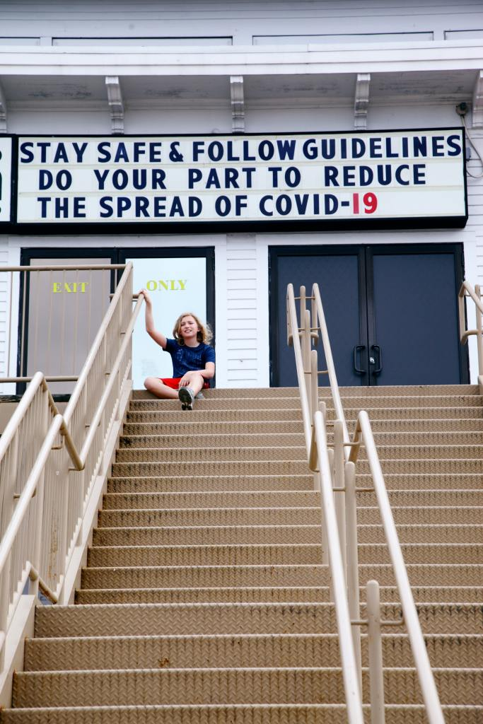 young person sitting by a covid-19 sign