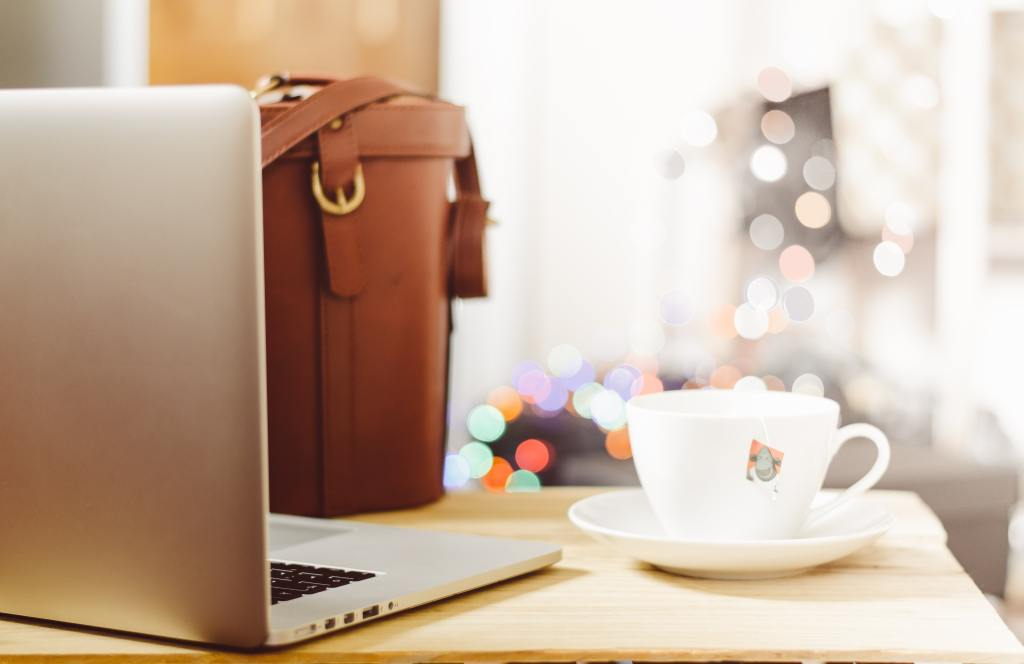 photo of a laptop, purse, and cup of coffee on a table