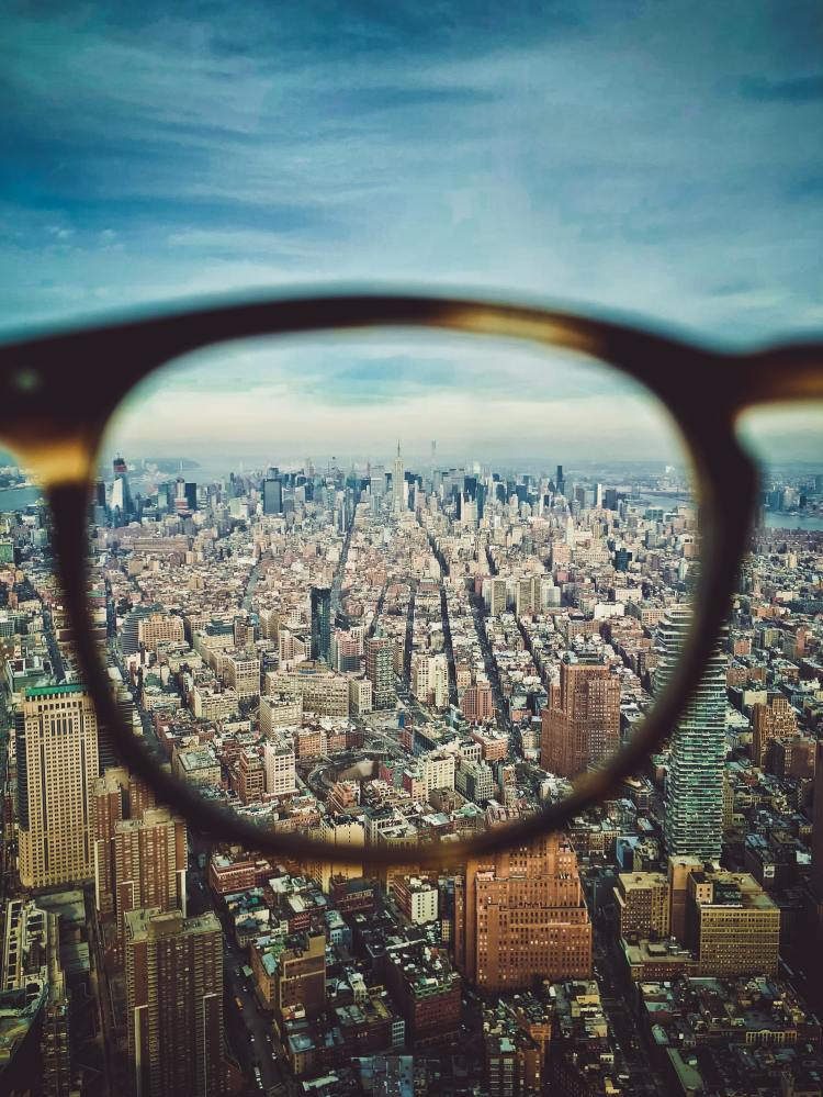 photo of a city seen through the lens of a pair of glasses