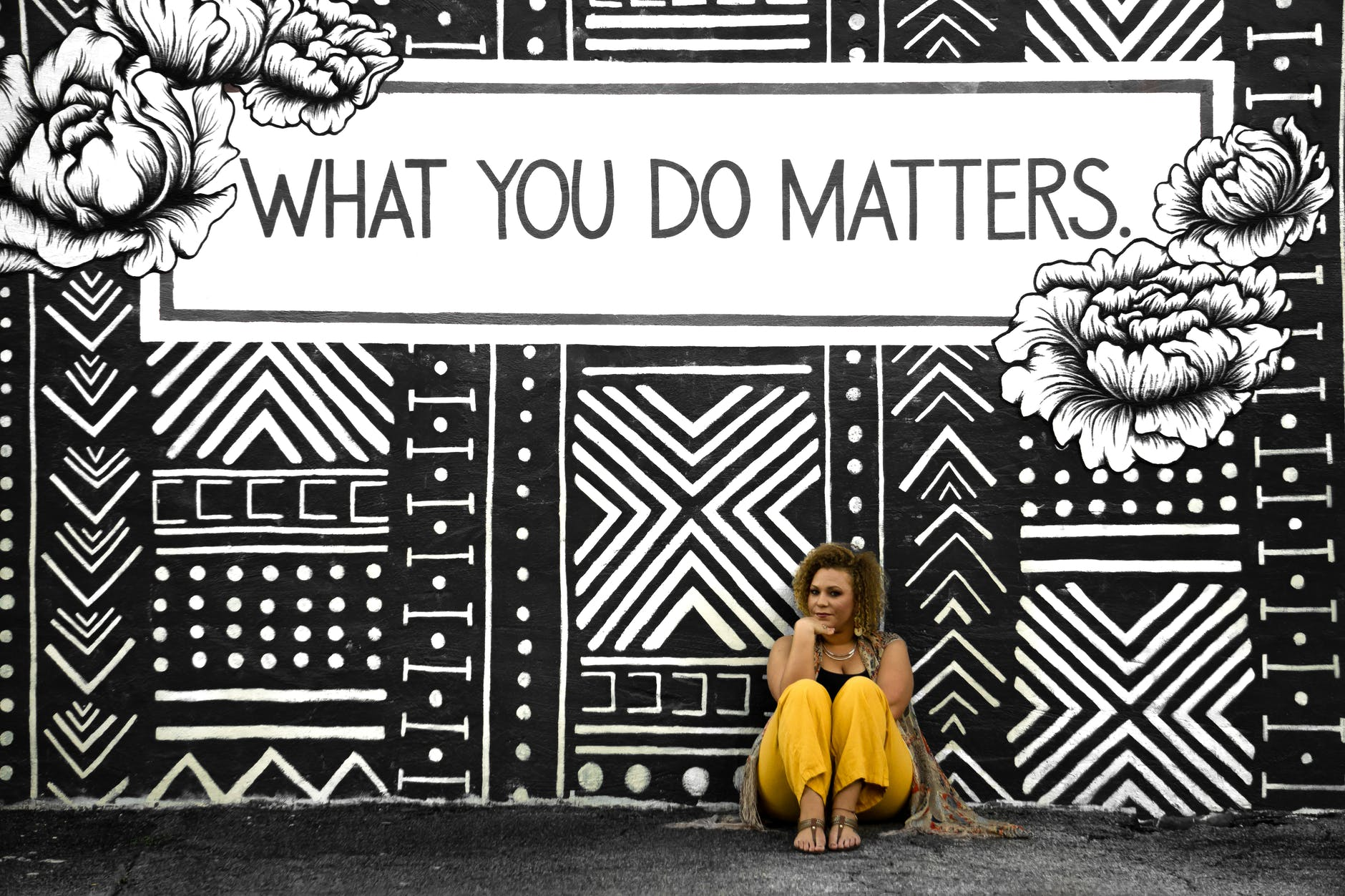 """photograph of a woman standing in front of a sign that says, """"what you do matters."""""""