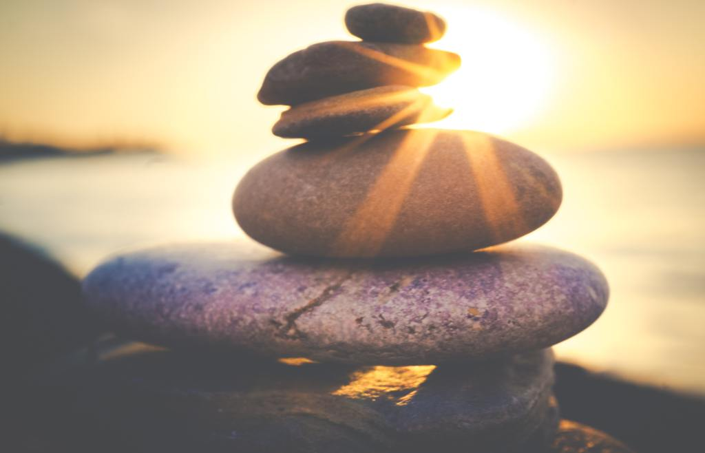 photo of a stack of rocks in nature, with bright rays of sunlight shining