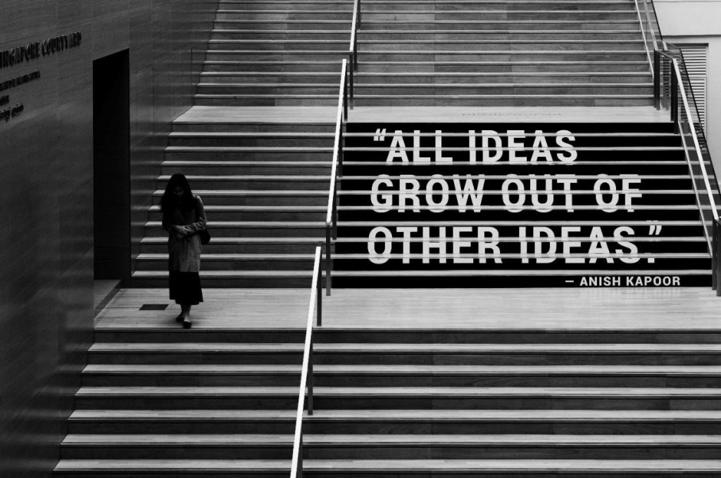 """photo of a woman walking down stairs superimposed with the quote """"all ideas grow out of other ideas"""" by anish kapoor"""