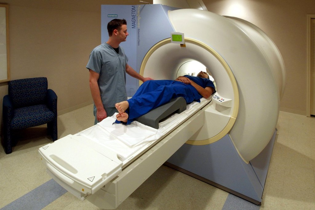 photo of an MRI technician scanning a person in an MRI