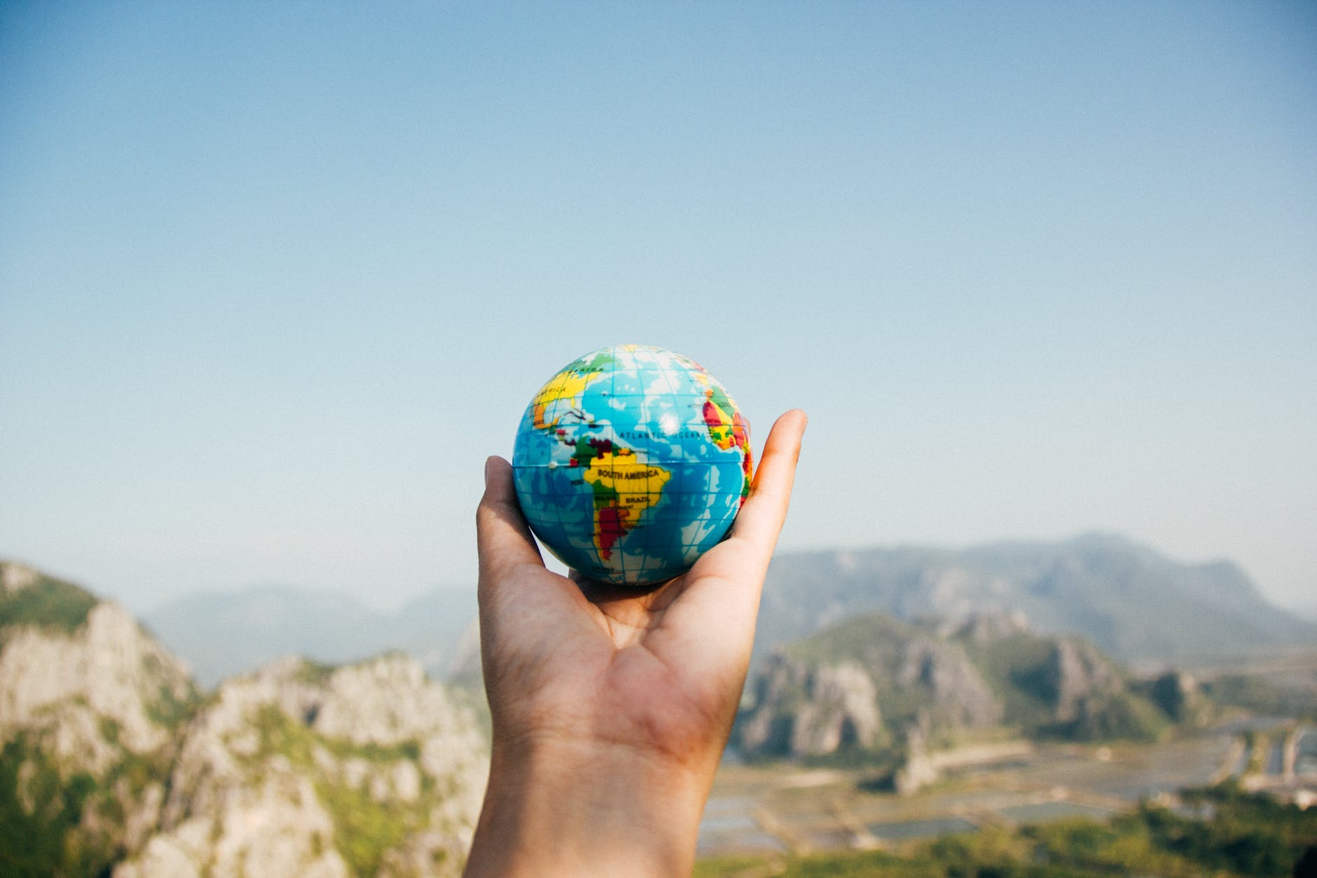 photo of a person holding a globe in their hand