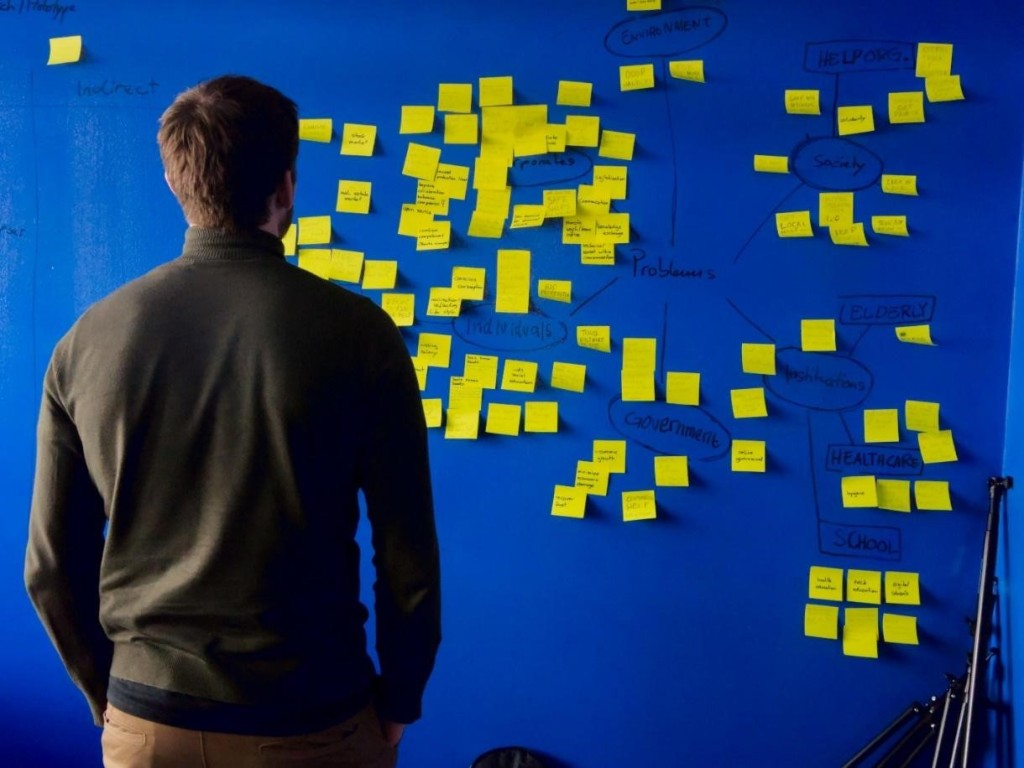 photo of a man standing in front of a bulletin board with many post-it notes