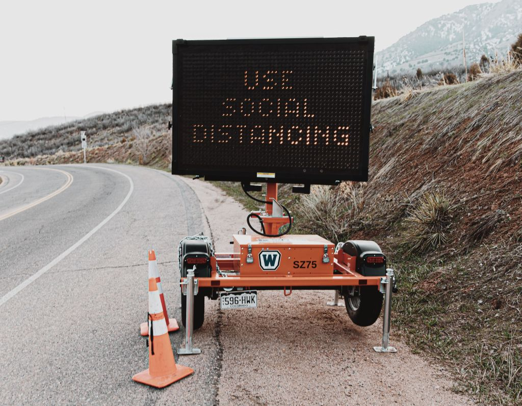 picture of road sign telling drivers to social distance