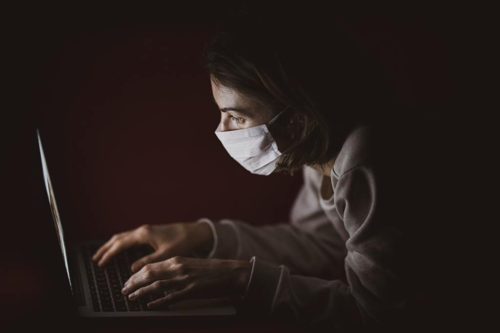 photo of a person wearing a mask working on a laptop