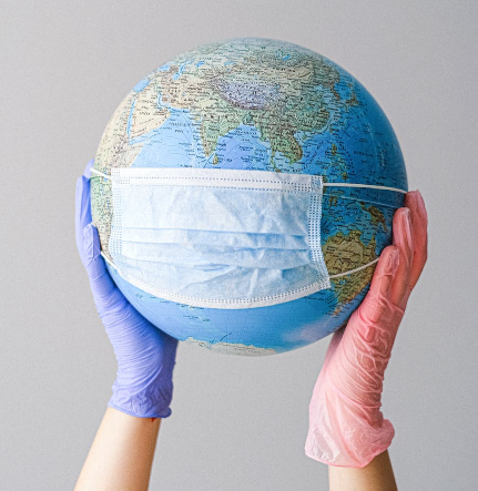 photo of gloved person holding up a globe wearing a facemask