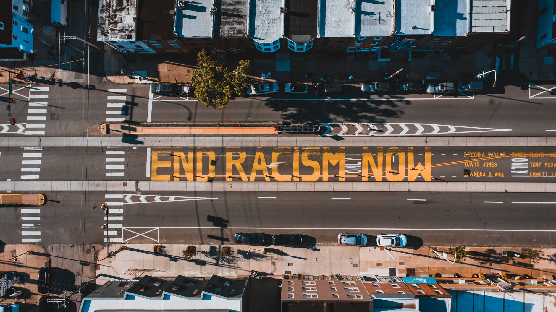 """birds'-eye-view photo of a street with the words """"end racism now"""" painted, in large letters, on it"""