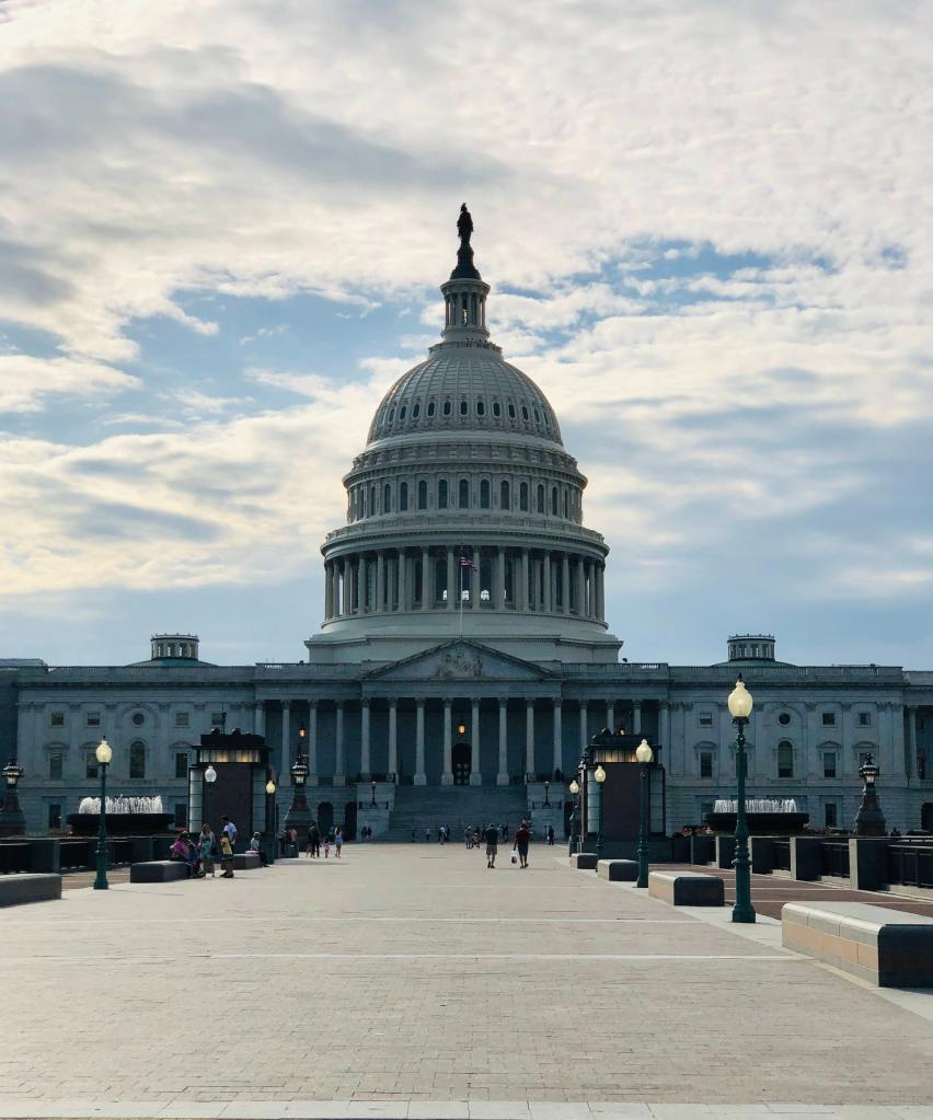 photo of visitors walking on a walkway in front of the u.s. capitol building