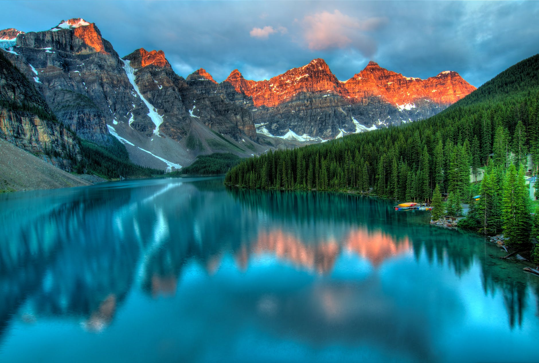 photo of a nature scene with a mountain range, trees, and a body of water