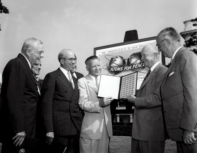 """photo of president eisenhower receiving an album of """"atoms for peace"""" stamps"""